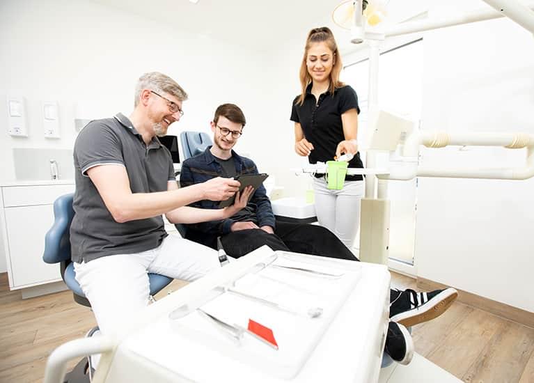 patient schaut gemeinsam mit dem zahnartzt auf ein ipad mobil