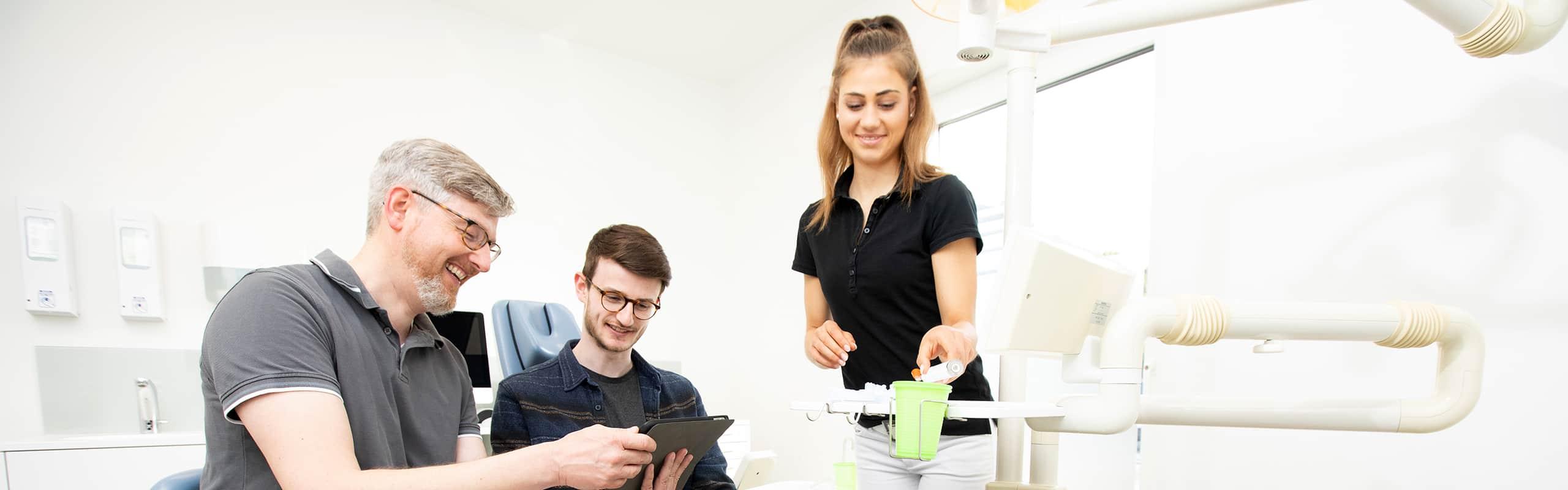 patient schaut gemeinsam mit dem zahnartzt auf ein ipad