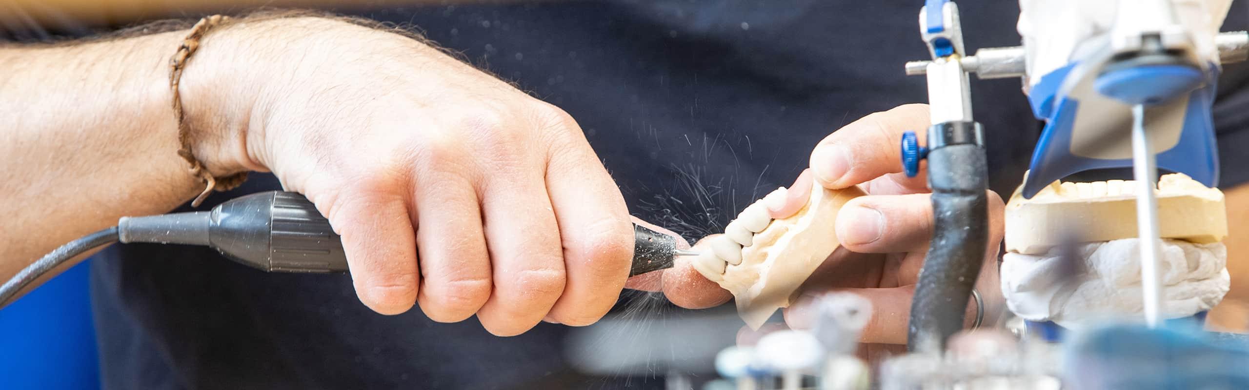 schleifen einer zahn prothese in der zahnarztpraxis von fausten und hahn